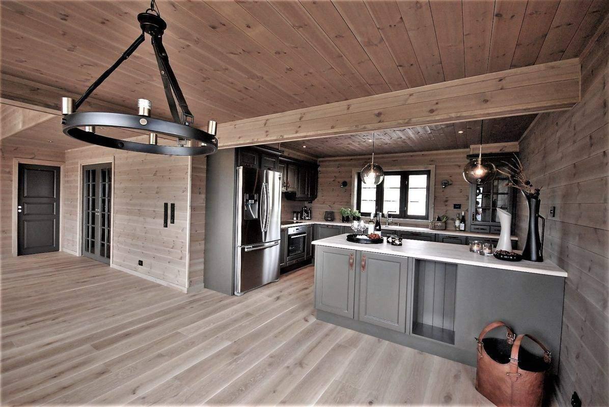 24 Hyttemodell Høgevarde 127. Spisestua og kjøkkenet. Dører, vinduer og kjøkkeninnredning i samme mørke gråf