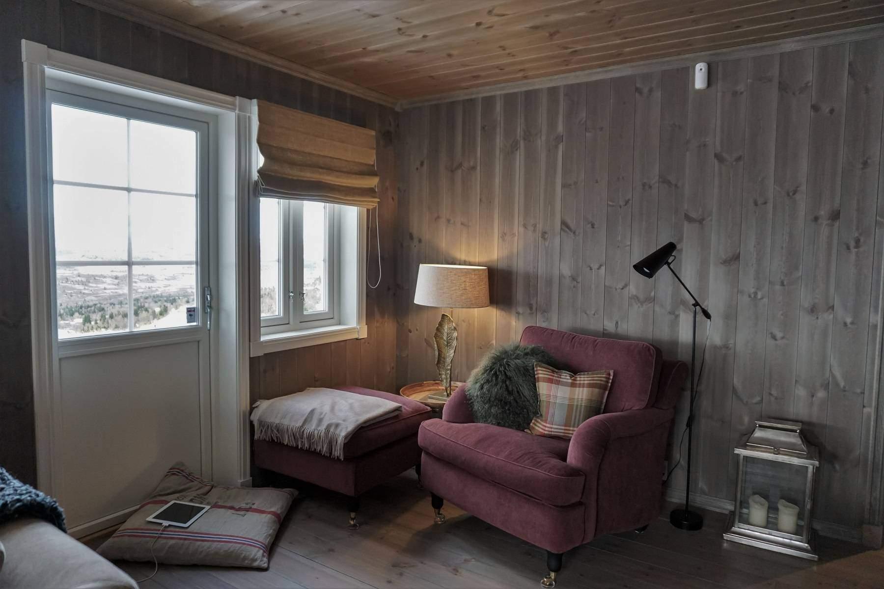 154 Hyttemodell Hytte Strynsfjell 122 Tiurtoppen Hytter.Lesekroken i stua med dør ut til en lun terrassekrok
